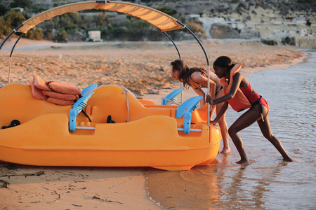 Girls pushing a pedalo on the beach Stock Photo