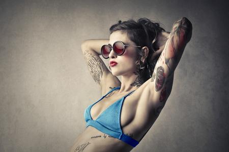 femme tatouée dans un maillot de bain bleu