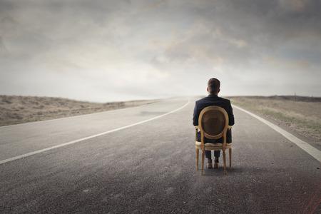 孤独な道に沿って座っている孤独な男 写真素材