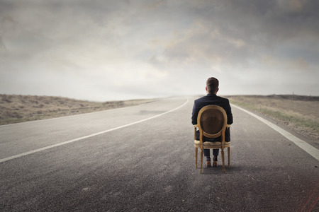 Hombre solo que se sienta a lo largo de un camino solitario Foto de archivo - 65801506