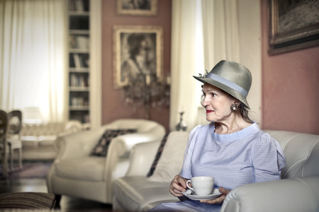 Classy elderly woman drinking a cup of tea photo