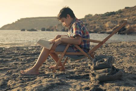 Kid reading a book at the beach photo