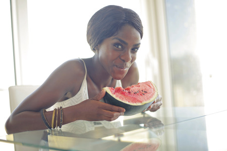 black woman is eating a watermelon photo