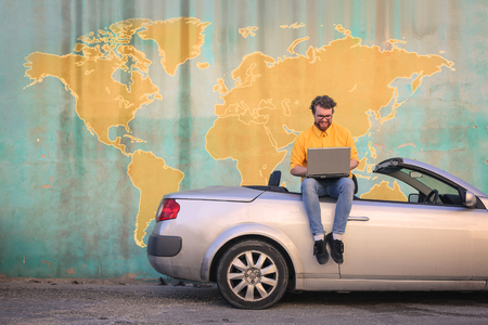 Man in yellow shirt sitting on his car Stock Photo