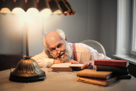 lamp light: Old man is reading a lot of books