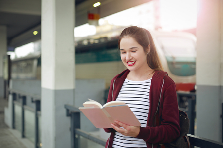 Happy girl is reading a book at the trainstation photo