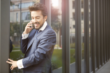 working on computer: Businessman is talking in the phone