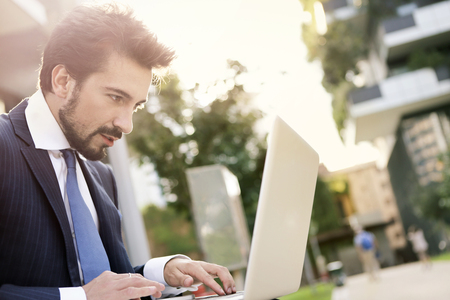 working on computer: Businessman is working outside