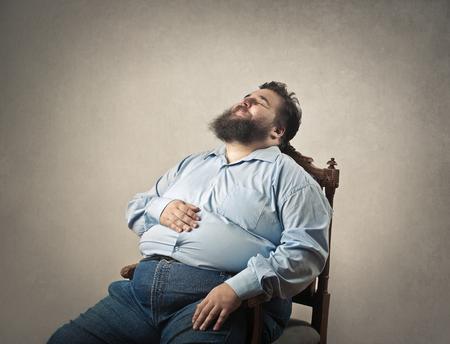 Fat man ligt te slapen op een stoel