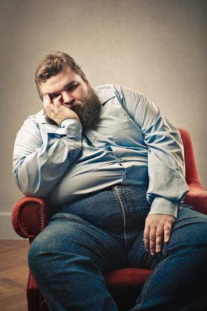 Grote kerel ligt te slapen in het airmchair