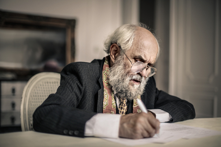 Old man is writing a letter Фото со стока