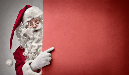 Santa Claus is pointing at the red wall Stock Photo