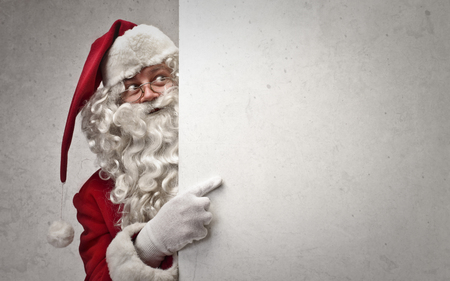 Santa Claus is pointing to the wall Stock Photo