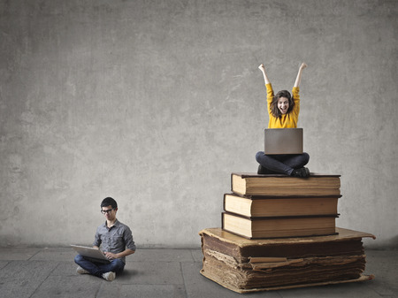 Boy is sitting on the ground and a girl is sitting on books Stock Photo