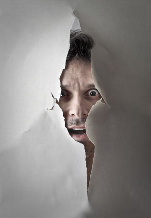 astonishment: Man is looking through a hole Stock Photo