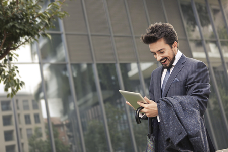 Businessman with his tablet on the street Stock Photo