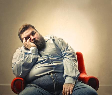 Fat man is sleeping in an armchair Stockfoto