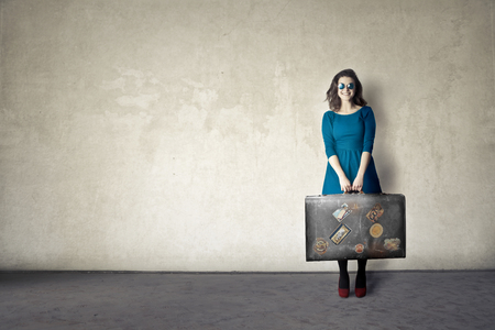 textured backgrounds: Woman in a blue dress is carrying a big suitcase