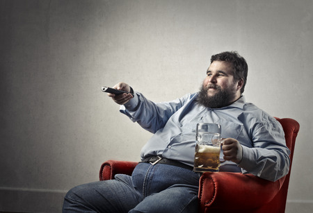 Fat guy is watching TV and drinking beer photo