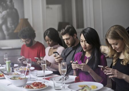 communication: Friend are texting at the dinner table