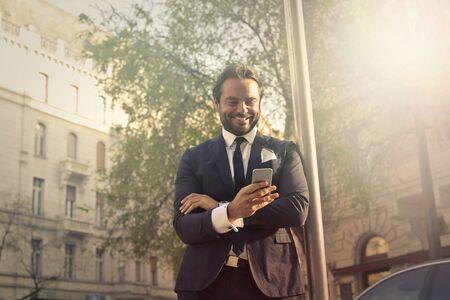 telephone: Happy businessman texting