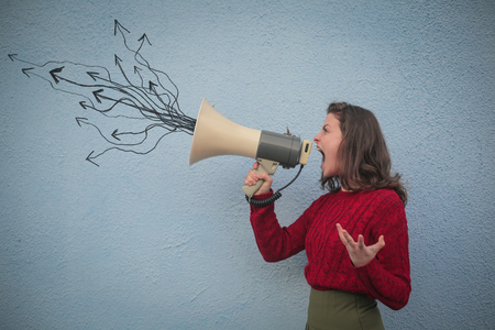 Brunette woman is screaming into the megaphone