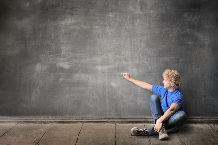 project: Blonde boy is drawing on the blackboard Stock Photo