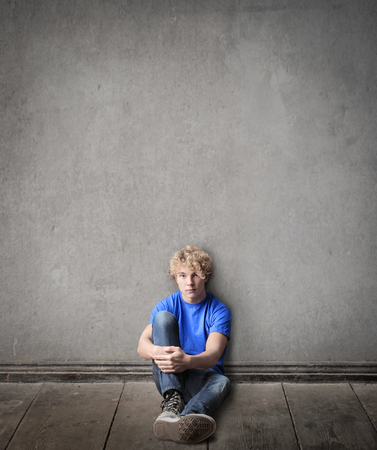 project: Young, blonde boy is sitting on the ground