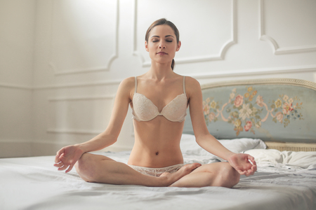 Woman is meditating in lingerie Stock Photo