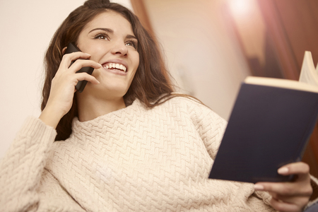 apartment: Beautiful girl is reading a book and speaking on the phone Stock Photo