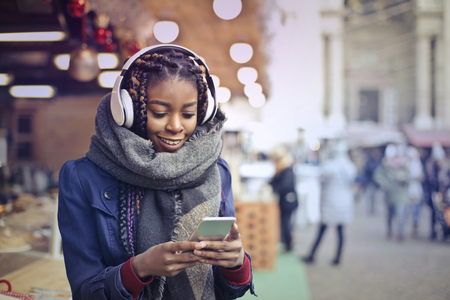 telephone: Black woman is texting on the street Stock Photo