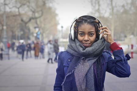 winter fashion: Happy African woman is listening to music