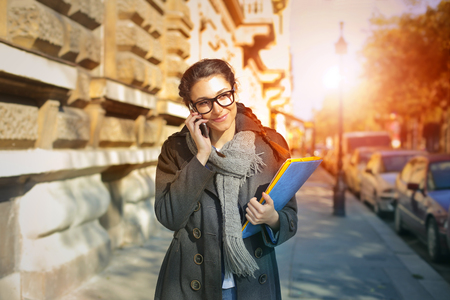 winter fashion: The woman is on the phone and carrying colorful folders