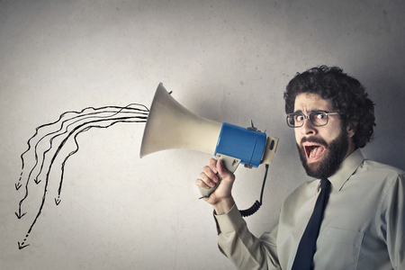 white work: Crazy man is screaming into the megaphone Stock Photo