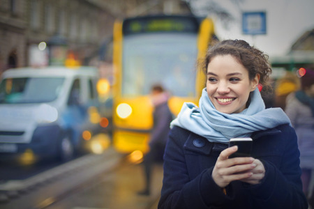 cold: Nice woman is texting in the tram stop