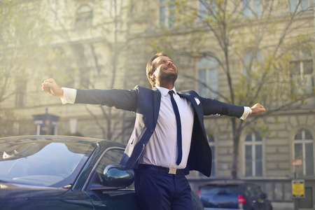 Happy businessman is dancing next to his car
