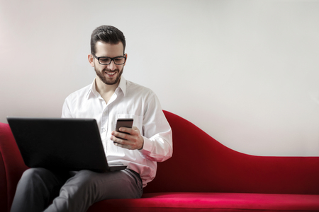 couch: The businessman is sitting on the sofa with his laptop and phone Stock Photo