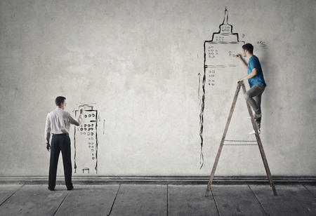 small scale: Two man are designing building on the wall Stock Photo