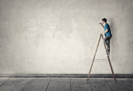 The man is writing on the wall from the top of the ladder photo