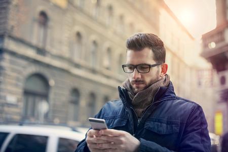 winter fashion: Businessman texting on the street