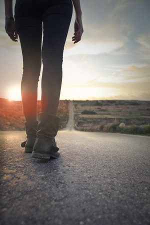 retro woman: Walking in boots in the sunset Stock Photo