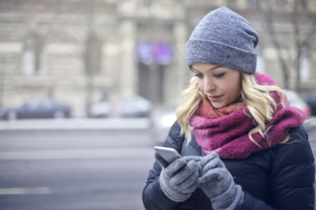 lady on phone: Young blonde girl is texting on the street