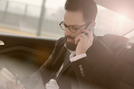 book: Businessman is traveling to work by car Stock Photo