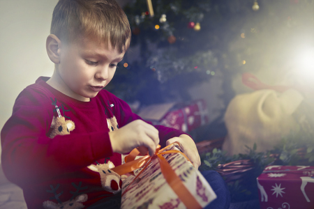 Happy child is opening a christmas present Stock Photo
