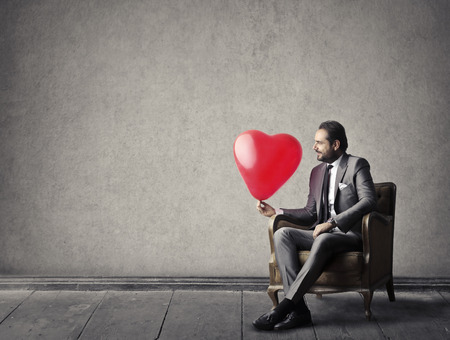 huge: A business man is holding a heart shaped balloon