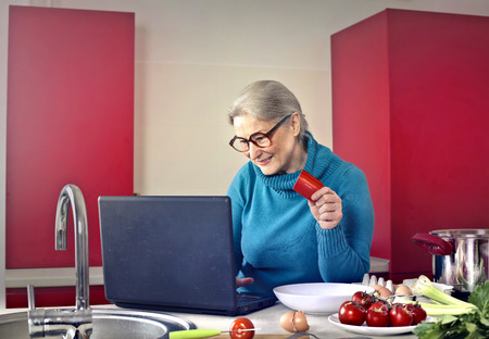 ingedient: Old lady is using her computer in the kitchen Stock Photo