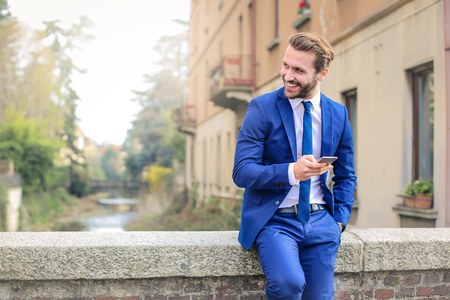 A handsome businessman is texting on a bridge