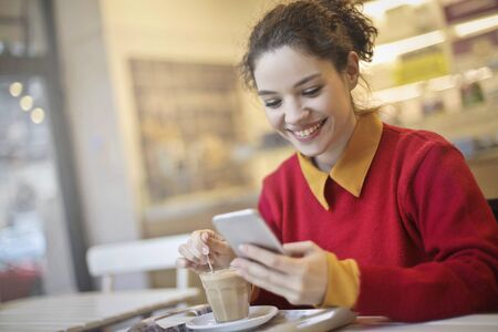 young lady: The young lady is texting next to a cup of coffie