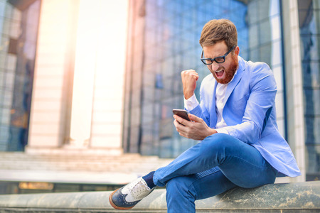 The businessman is shouting at his smartphone Stock Photo