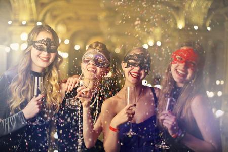 여자의 그룹은 마스크를 착용하고 파티를하고 있습니다
